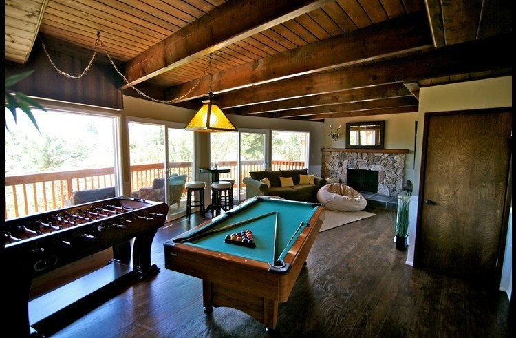 Game room on lower level with pool table, foosball and wood burning fireplace