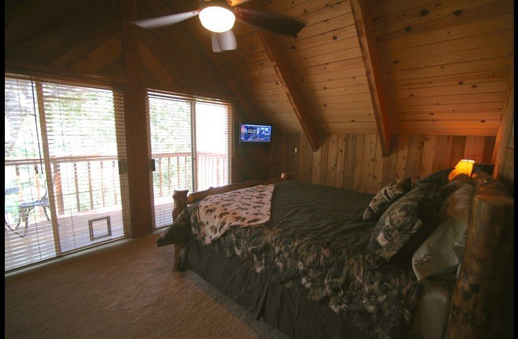 Master bedroom with flat screen TV and private deck