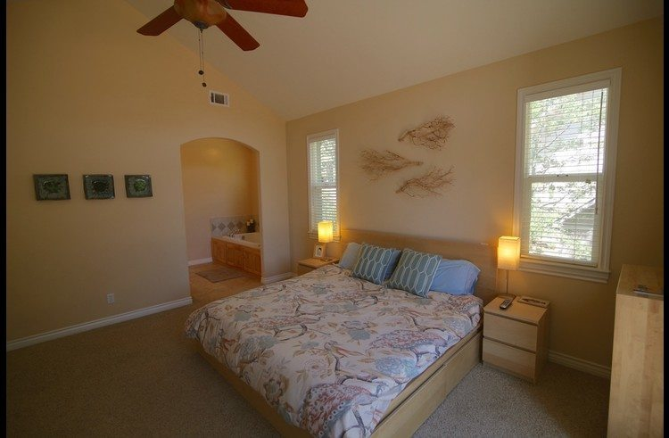 Master bedroom with vaulted ceilings and ceiling fan