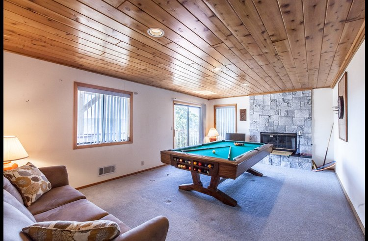 Game room with pool table and fireplace