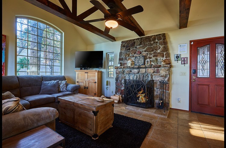 Wood burning fireplace surrounded by stone in the living room
