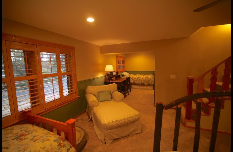 Guest room on lower level with sitting area, desk and twin bed in the background
