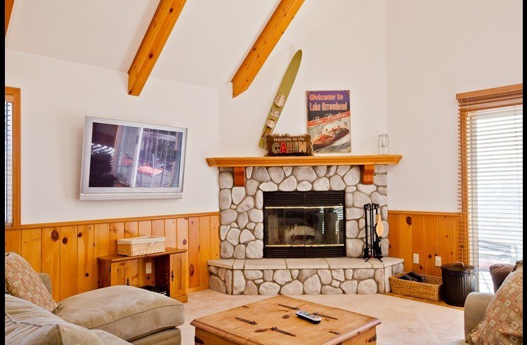 Flat screen TV and wood burning fireplace surrounded by stone