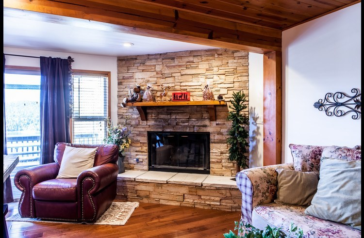 Wood burning fireplace in sitting area next to kitchen and dining room