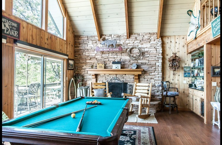 Pool table and wood burning fireplace surrounded by ledger stacked stone