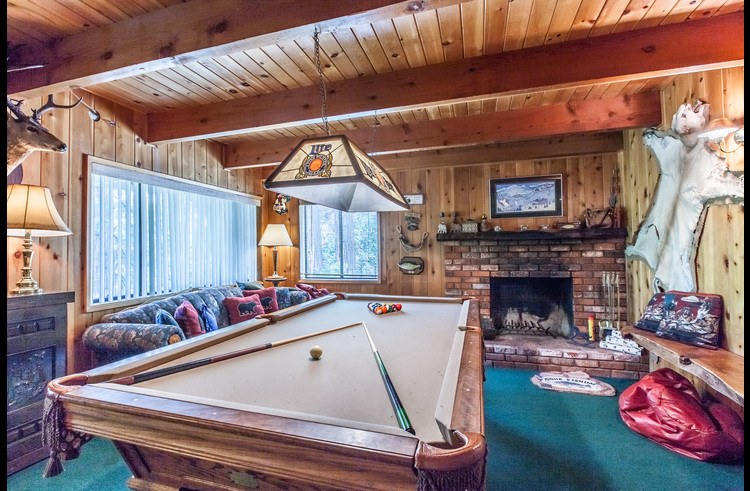 Game room with pool table and wood burning fireplace