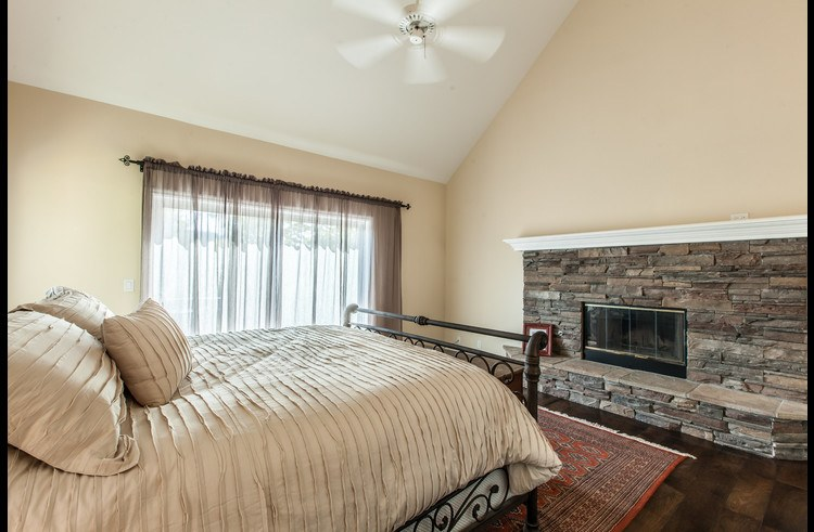 Master bedroom with wood burning fireplace surrounded by stone
