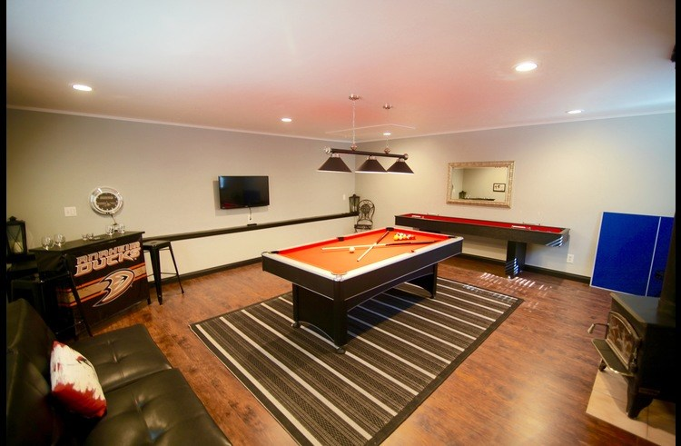 Pool table, shuffle board, couch and bar in the game room