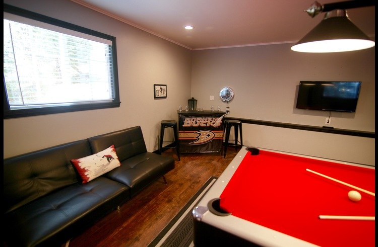 couch, bar and flat screen TV mounted on the wall