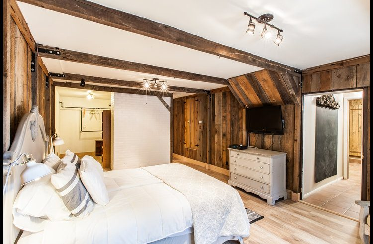 Master bedroom with reclaimed wood walls and flat screen TV