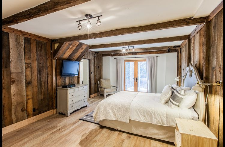 Master bedroom with exposed beams and reclaimed wood walls