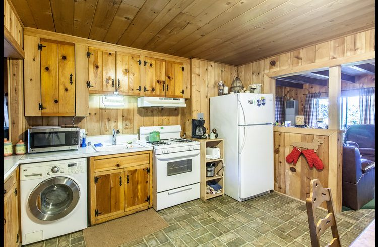 Kitchen with rustic knotty pine cabinets and combo washer/dryer