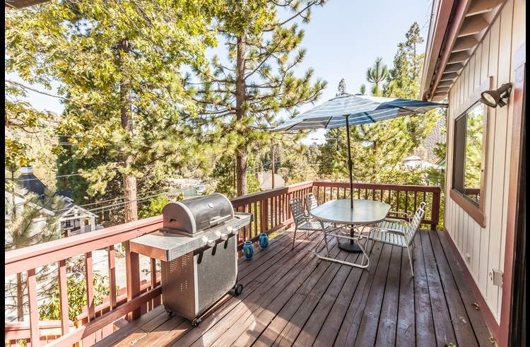 Deck on the main level with patio furniture and gas BBQ