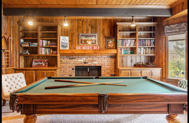 Game room near the entry with pool table and wood burning fireplace