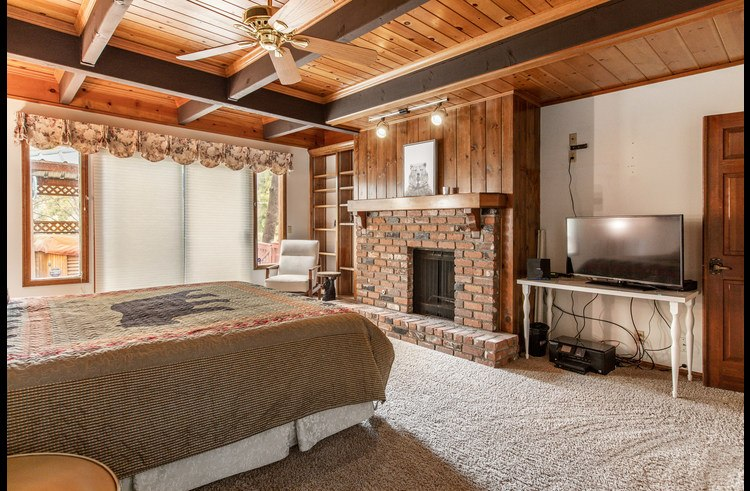 Wood burning fireplace and flat screen TV in the master bedroom