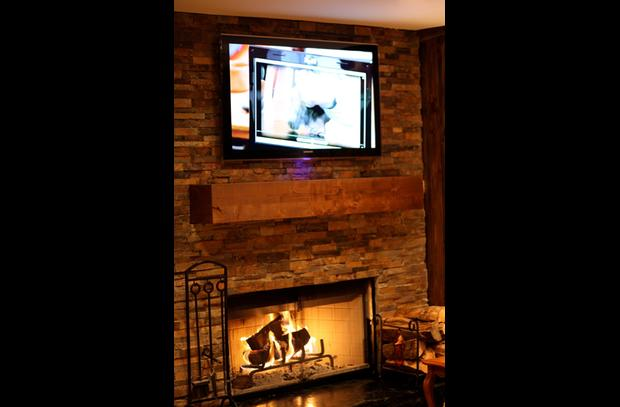 Flat screen Samsung and ledger stack stone wood burning fireplace