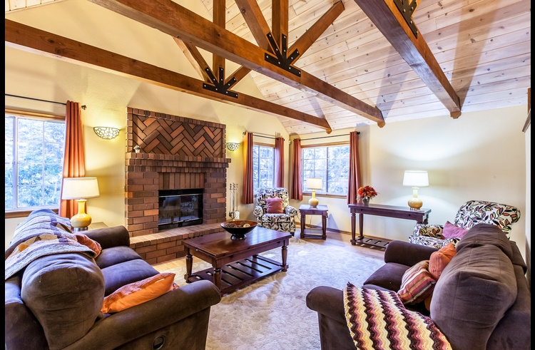 Living room with vaulted ceilings and wood burning fireplace