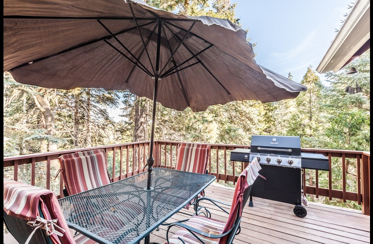 Deck off the living room with patio furniture and gas BBQ