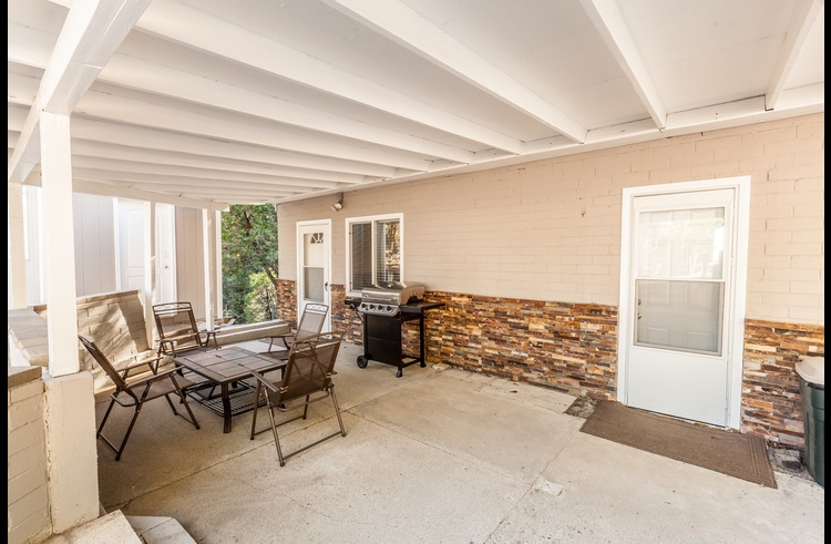 Large covered patio with outdoor furniture and propane BBQ.