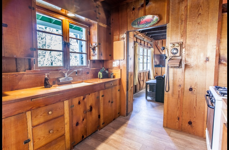 Classic cabin with with original 1920's knotty pine cabinets in the kitchen