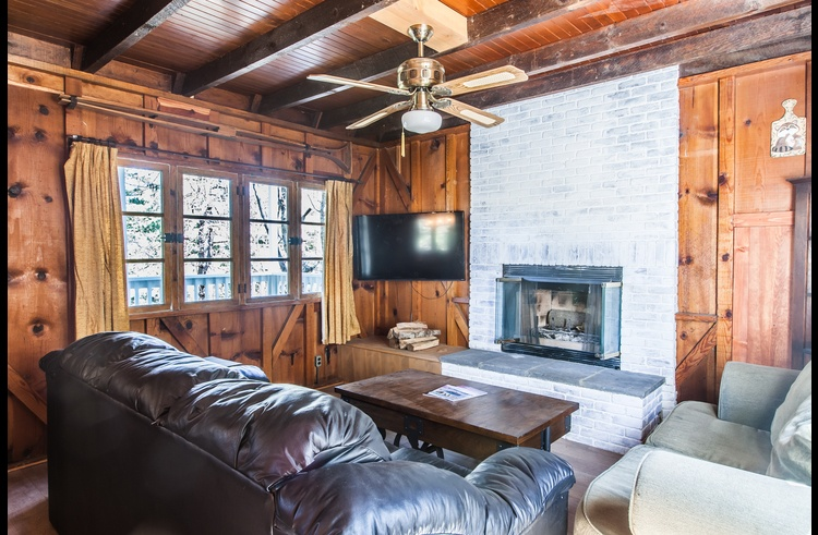 Living room with flat screen TV and wood burning fireplace