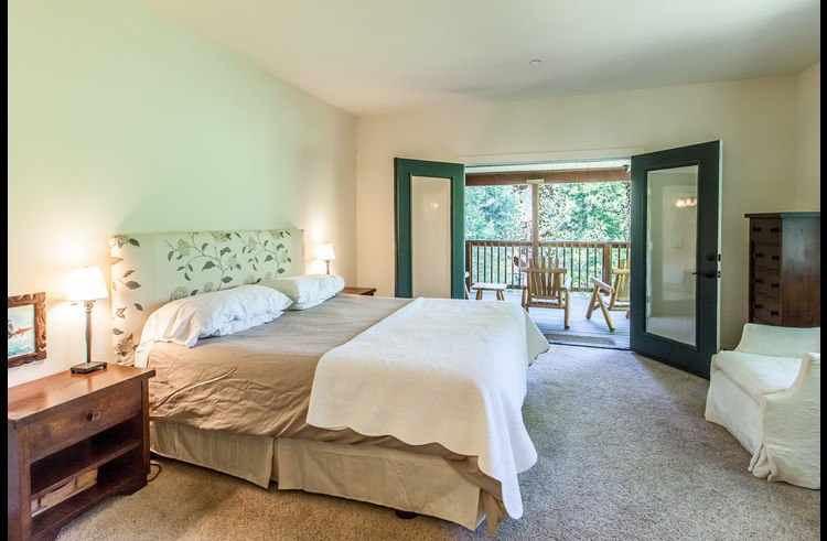 Master bedroom on main level with french doors leading to covered deck