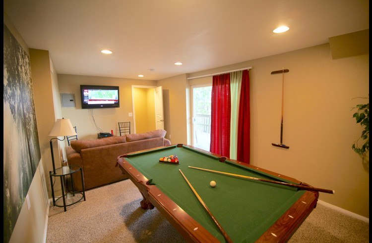 Pool table with couch and flat screen TV