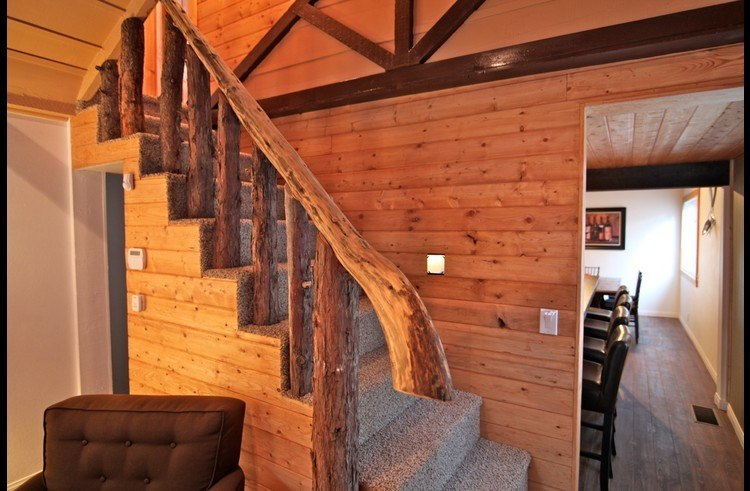 Living Room with stairs to upper level and custom railing made from cedar trees