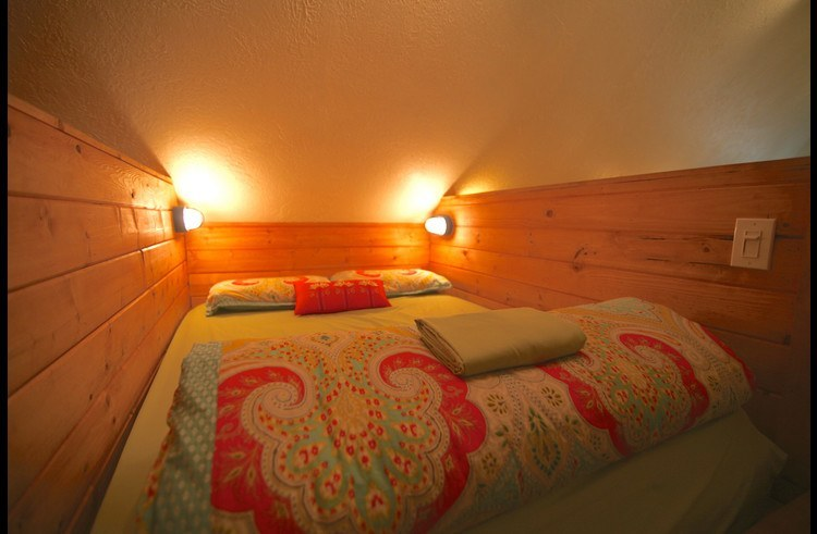 3 sleeping bay with full size beds surround by knotty pine wood