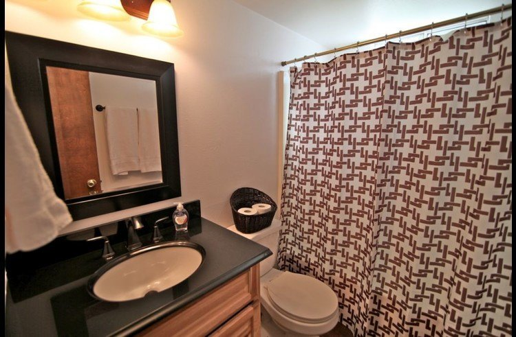 Full bathroom on lower level with black granite counter top