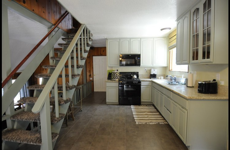 Kitchen with stairs leading to upper level