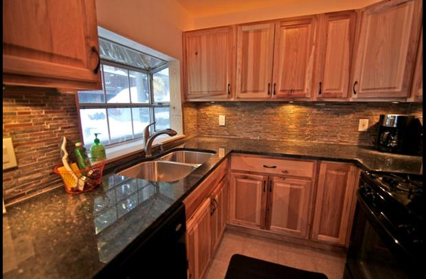Hickory cabinets with black granite counter and slate backsplash