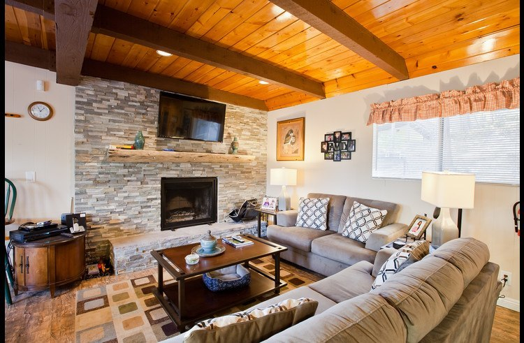 Living room with wood burning fireplace surrounded by ledger stacked stone