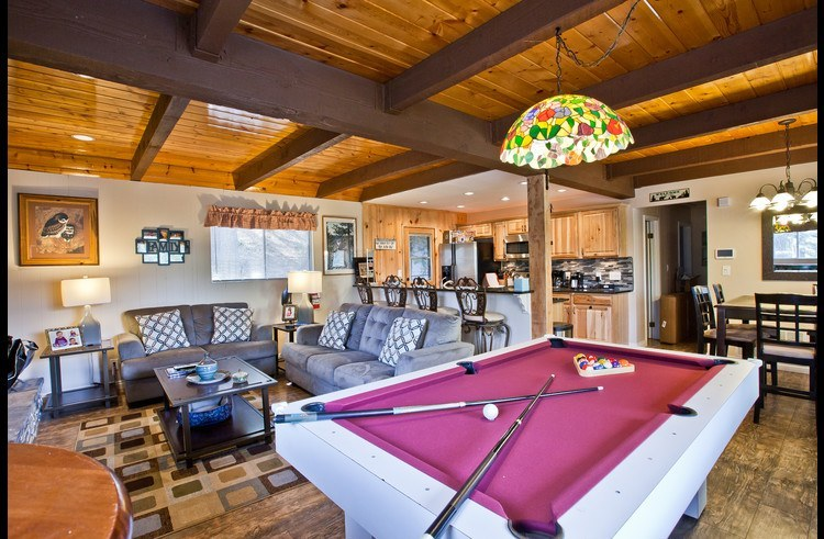 Pool table with living room and kitchen in the background