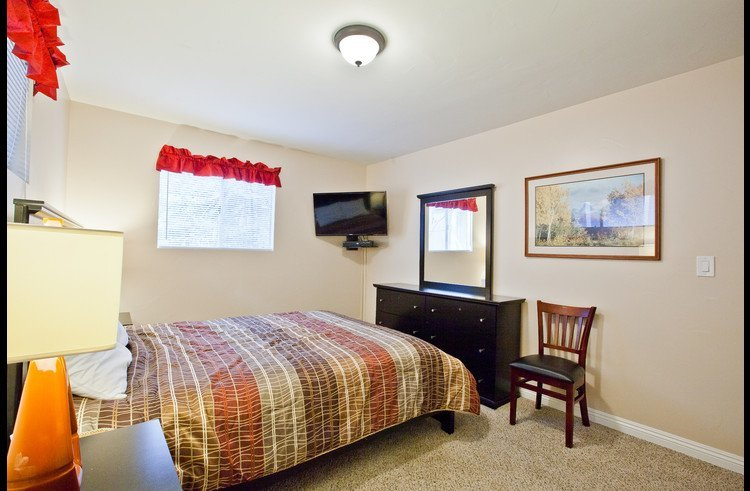 Guest room 1 on main level with queen bed and flat screen TV