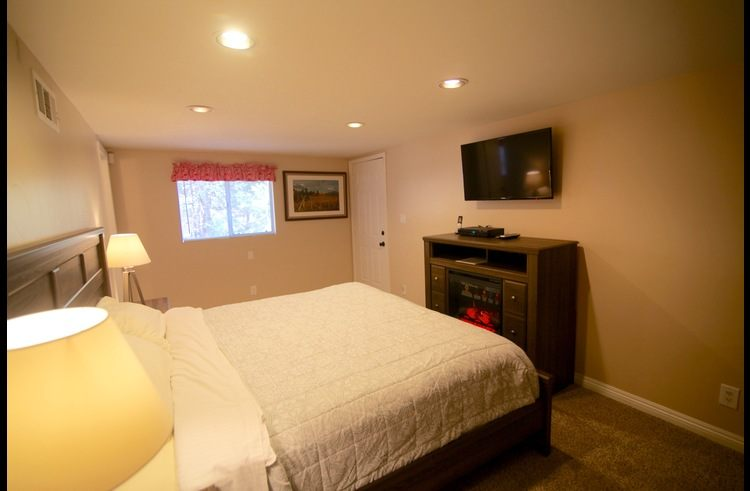 Master bedroom with electric fireplace and flat screen TV