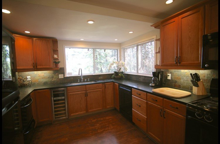 Large kitchen with soap stone counters and slate tile backsplash