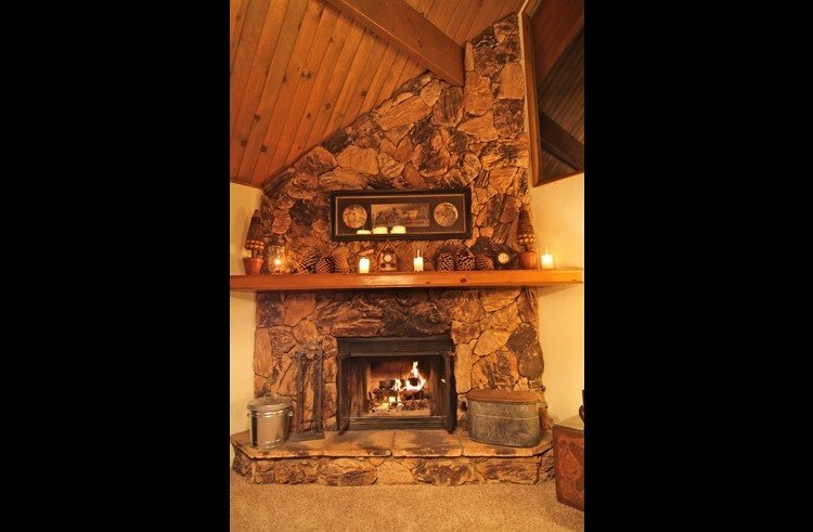 Floor to ceiling stone with wood burning rock fireplace. Flat screen TV to left of FP