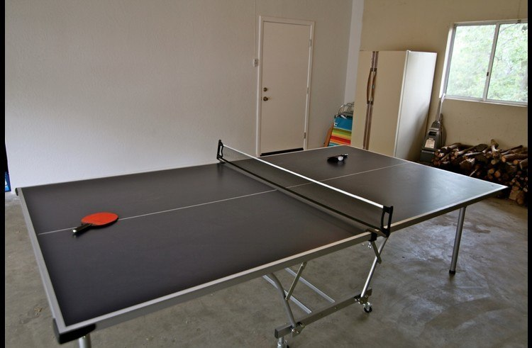 Ping pong table in garage plus a second refrigerator