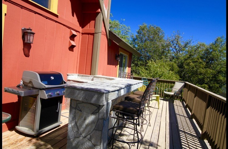 Natural gas Weber BBQ on upper deck with stone counter and barstools