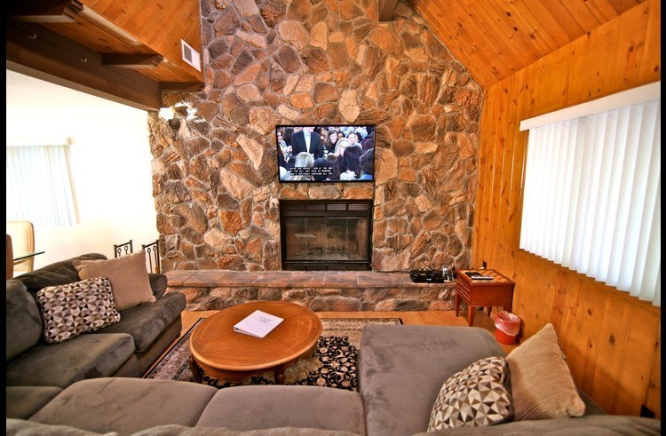 Flat screen TV above wood burning fireplace in family room