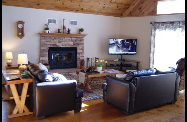 Large flat screen TV and wood burning fireplace