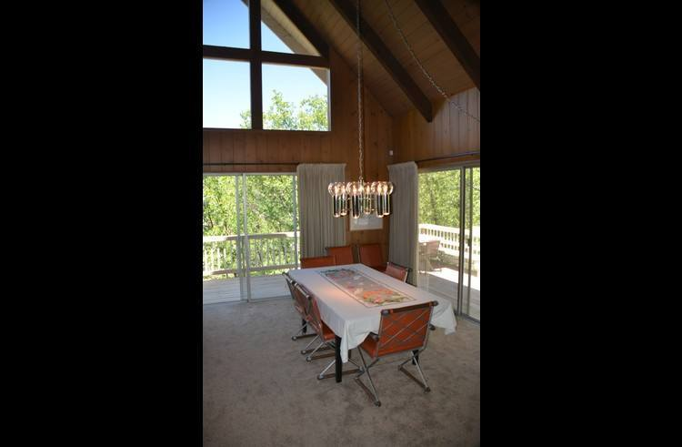 Dining table next to living room that extends to accommodate 10 with chairs for 10.