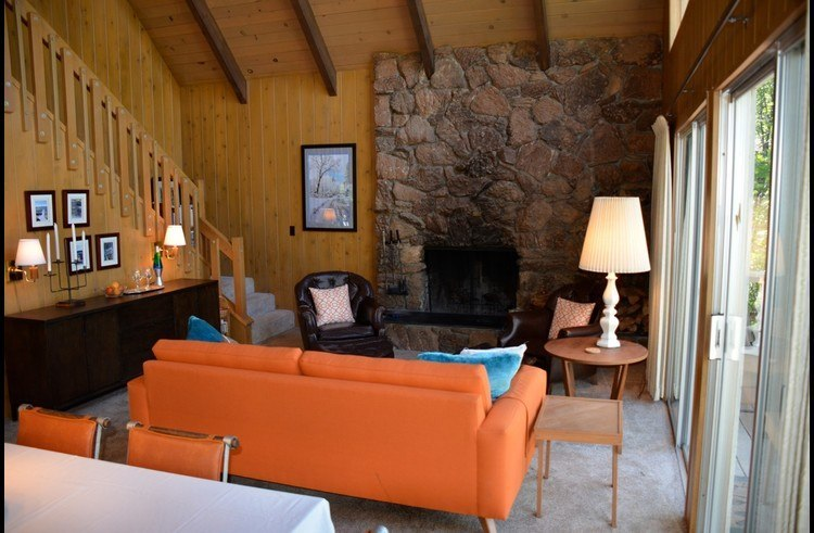 Living room with wood burning fireplace surrounded by stone